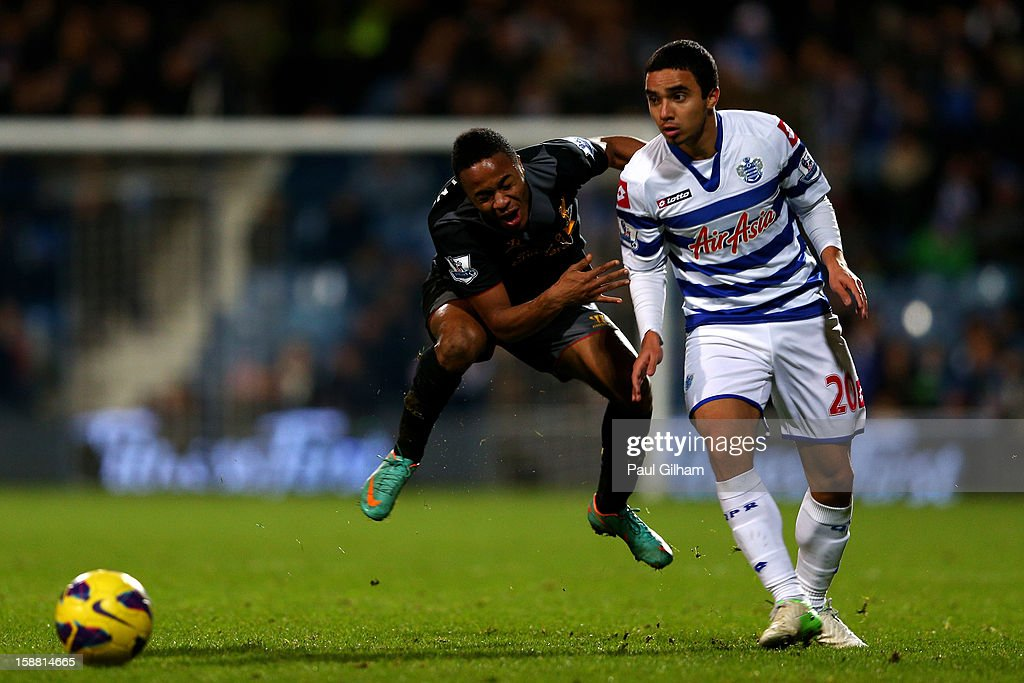 Raheem Sterling of Liverpool is shouldered off the ball by Fabio da Silva of QPR during the Barclays Premier League match between Queens Park Rangers and Liverpool at Loftus Road on December 30, 2012 in London, England.