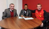 Raheem Sterling of Liverpool signs a new contract with Ian Ayre managing director and Brendan Rodgers manager Liverpool FC at Melwood Training Ground...