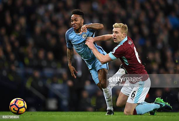 Raheem Sterling of Manchester City and Ben Mee of Burnley battle for possession during the Premier League match between Manchester City and Burnley...