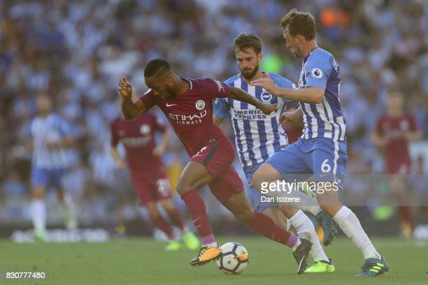 Raheem Sterling of Manchester City attempts to get away from Dale Stephens of Brighton and Hove Albion and Davy Propper of Brighton and Hove Albion...