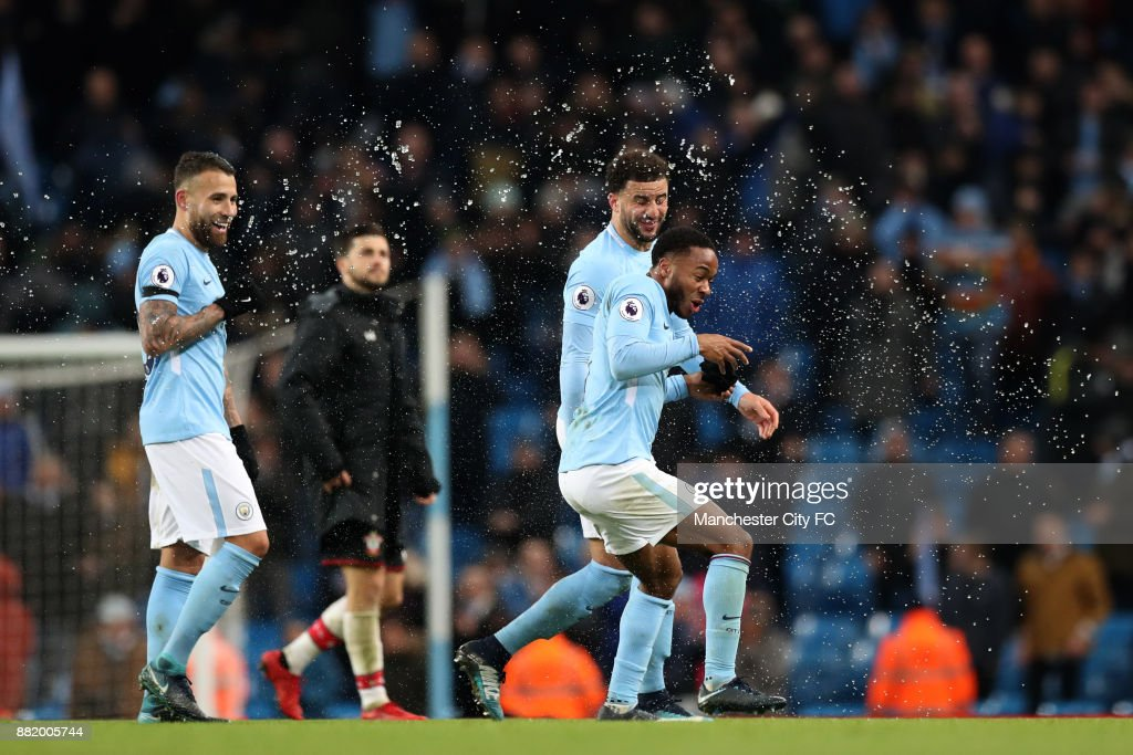 Raheem Sterling of Manchester City celebrates victory with Nicolas Otamendi of Manchester City during the Premier League match between Manchester City and Southampton at Etihad Stadium on November 29, 2017 in Manchester, England.