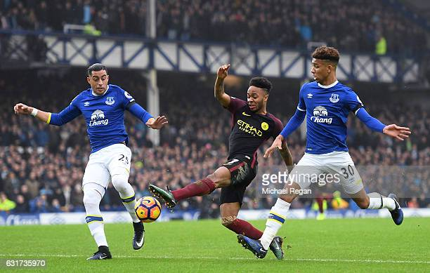 Raheem Sterling of Manchester City is closed down by Ramiro Funes Mori and Mason Holgate of Everton during the Premier League match between Everton...