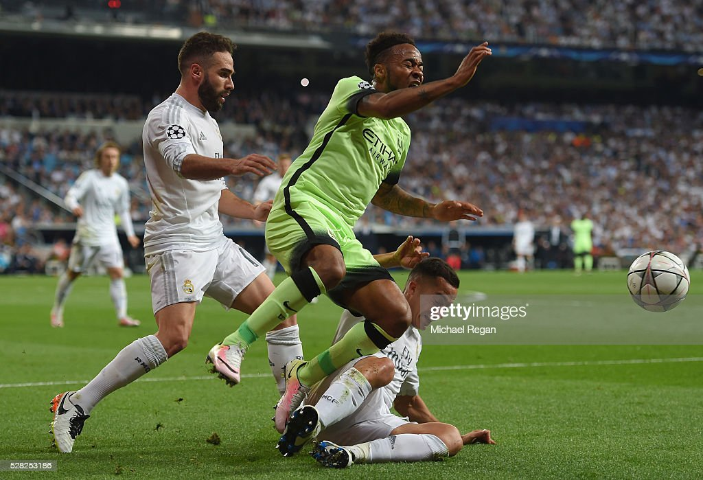 Raheem Sterling of Manchester City is tackled by Lucas Vazquez of Real Madrid and Daniel Carvajal of Real Madrid during the UEFA Champions League semi final, second leg match between Real Madrid and Manchester City FC at Estadio Santiago Bernabeu on May 4, 2016 in Madrid, Spain.