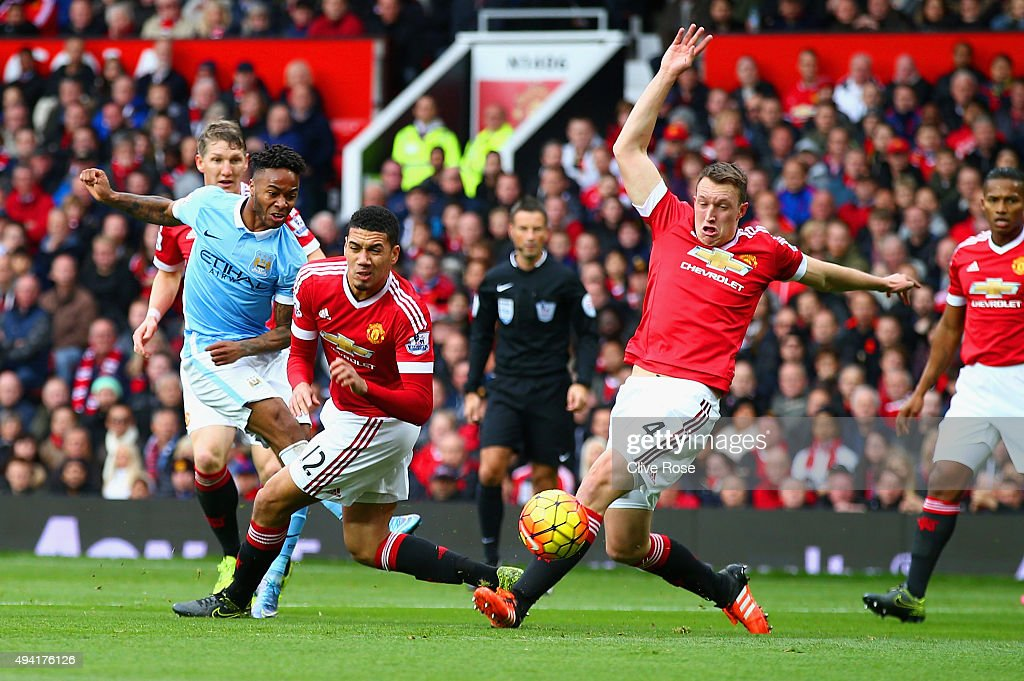 <a gi-track='captionPersonalityLinkClicked' href=/galleries/search?phrase=Raheem+Sterling&family=editorial&specificpeople=6489439 ng-click='$event.stopPropagation()'>Raheem Sterling</a> (L) of Manchester City shoots at goal while <a gi-track='captionPersonalityLinkClicked' href=/galleries/search?phrase=Chris+Smalling&family=editorial&specificpeople=5964313 ng-click='$event.stopPropagation()'>Chris Smalling</a> and <a gi-track='captionPersonalityLinkClicked' href=/galleries/search?phrase=Phil+Jones+-+Soccer+Player&family=editorial&specificpeople=7841291 ng-click='$event.stopPropagation()'>Phil Jones</a> of Manchester United attempt to block during the Barclays Premier League match between Manchester United and Manchester City at Old Trafford on October 25, 2015 in Manchester, England.