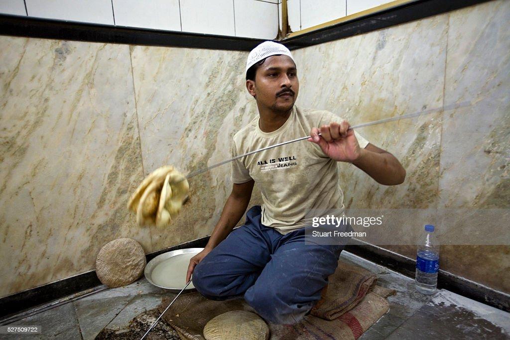 L M Rahman throws fresh naan bread from the tandoor to a a waiter at Karim's Restaurant Delhi India Karim's is a Delhi landmark was started by Haji...