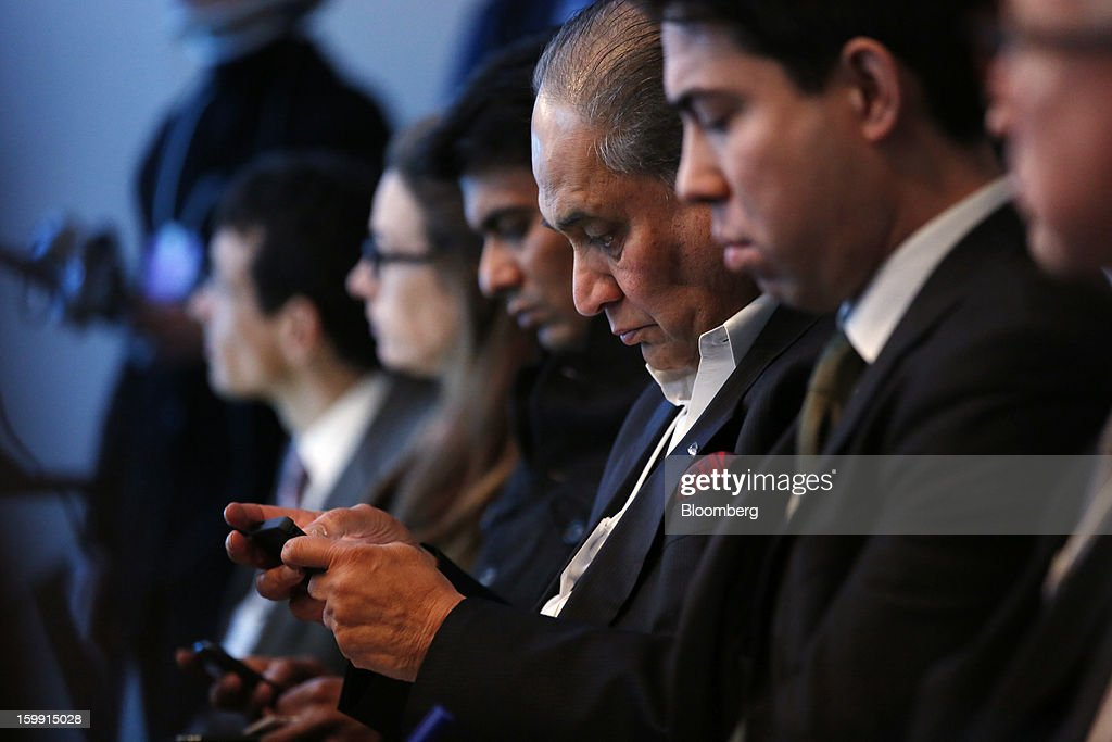 Rahul Bajaj, Indian billionaire and chairman of Bajaj Auto Ltd., center, checks his mobile phone at the start of a forum session on the opening day of the World Economic Forum (WEF) in Davos, Switzerland, on Wednesday, Jan. 23, 2013. World leaders, influential executives, bankers and policy makers attend the 43rd annual meeting of the World Economic Forum in Davos, the five day event runs from Jan. 23-27. Photographer: Jason Alden/Bloomberg via Getty Images