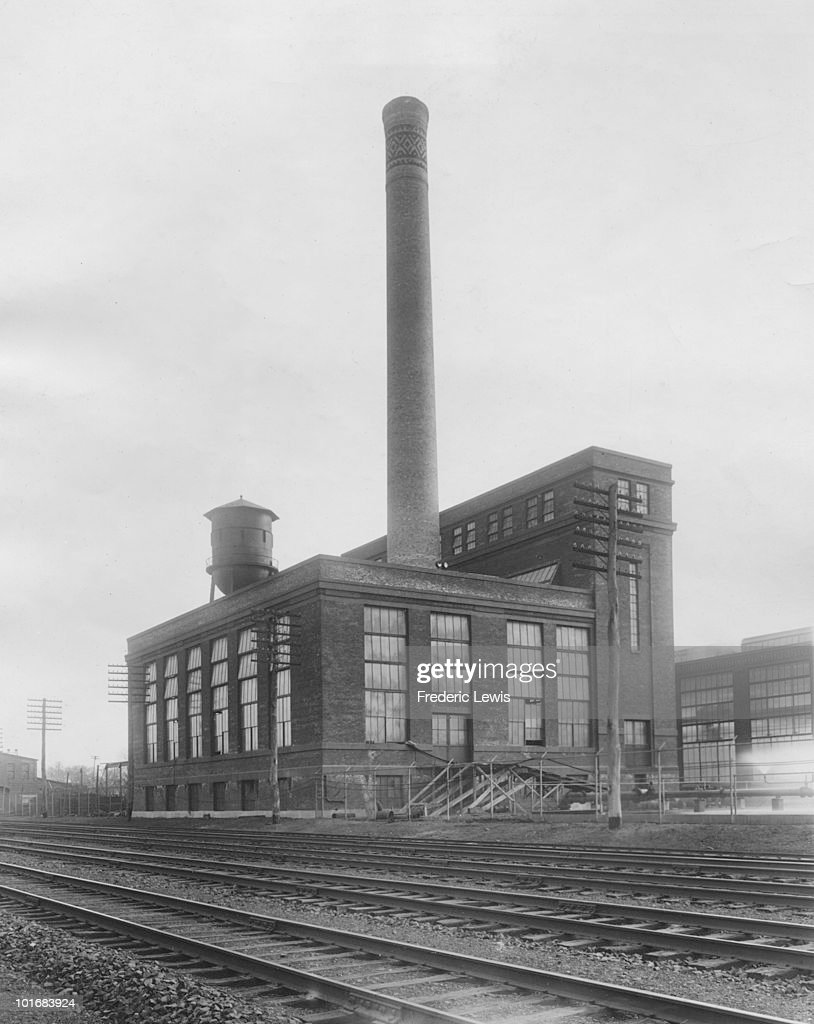 rail lines pass by a factory building with a water tower and smokestack rising from the