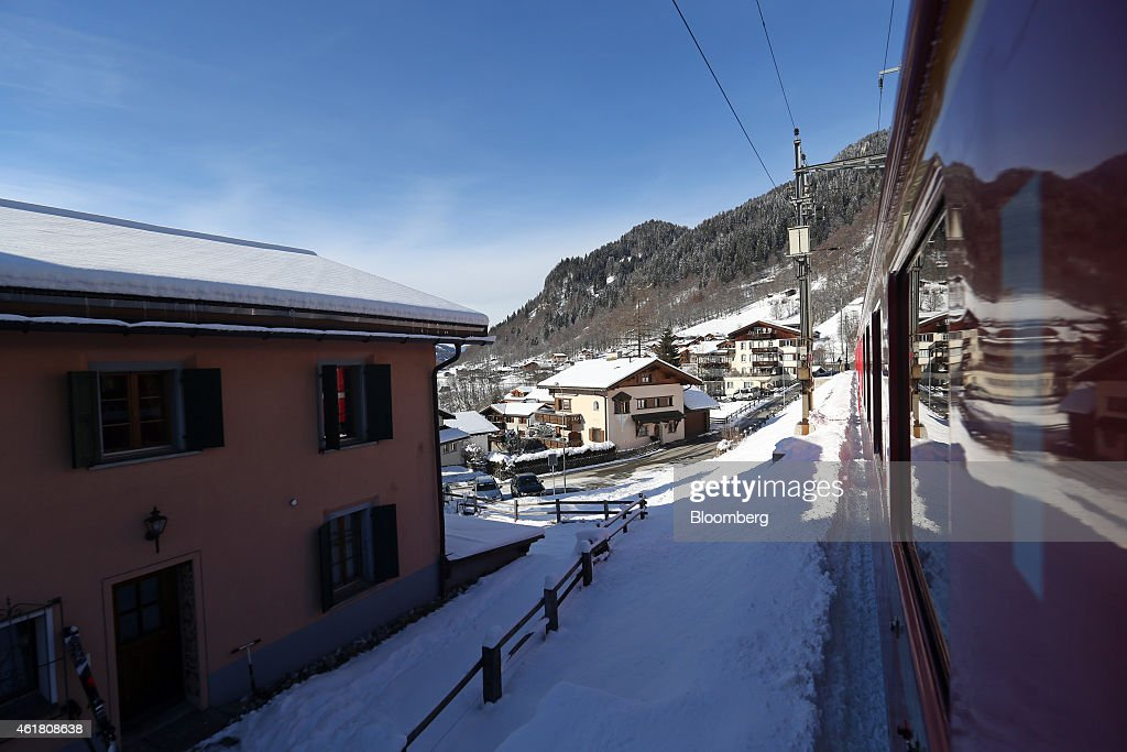 A rail passenger train operated by Rhaetian Railway passes traditional chaletstyle residential apartment buildings as it leaves Klosters Switzerland...