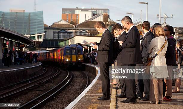 Rail passengers stand and wait for trains on platforms at Clapham Junction railway station in London UK on Tuesday Sept 18 2012 UK rail fares will...