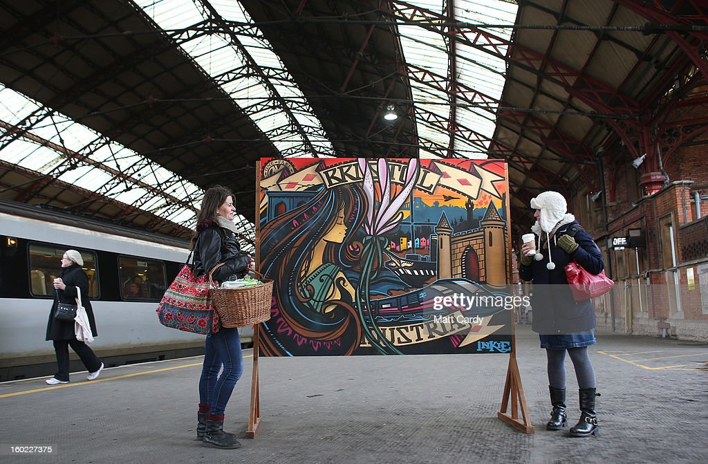 Rail users Lizzie Jones (L) and Jools Samson (R) stop to look at piece of graffiti art by Bristol born artist Inkie, which was unveiled to launch a brand new creative commissioning project for the Bristol Temple Quarter Enterprise Zone, on January 28, 2013 in Bristol, England. The work, titled 'Bristol to Brooklyn', will be on display at Bristol's Temple Meads train station and will welcome visitors to the city as they arrive in the spiritual home of the UK graffiti scene and internationally renowned artist Banksy
