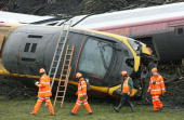 Rail workers walk past the derailed Virgin Express as it lies on its side after the fatal crash on February 25 2007 in Grayrigg Cumbria England One...
