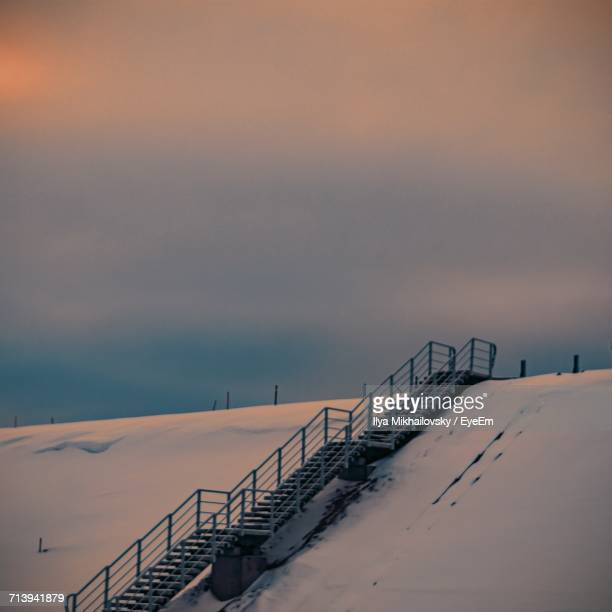Railing On Snow Covered Field Against Sky
