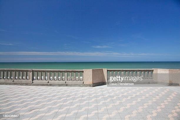 Railing on walkway overlooking ocean