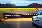 Fast train passing a railway crossing; cars waiting.Related images: