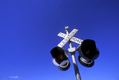 Grungy railroad crossing signal with bullet holes against a dark blue sky. A small cloud floating on the horizon adds balance to the image.