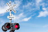 Railroad Crossing with Wispy Cloud in Blue Sky behind, Mojave Desert, California, USA.