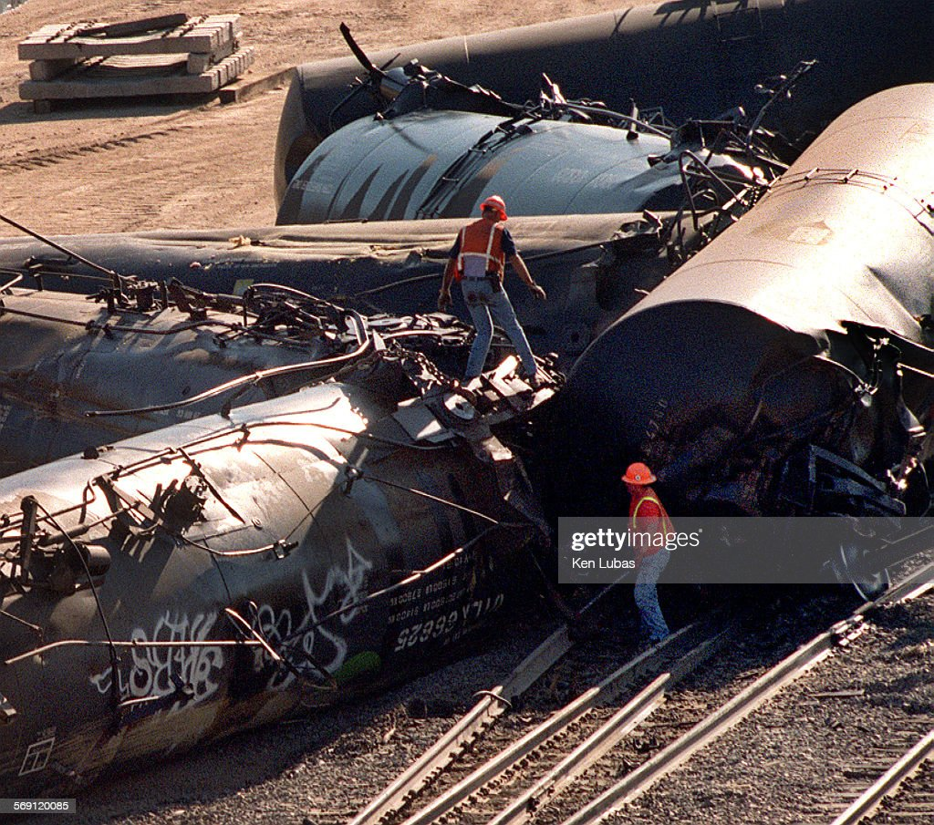Railroad emergency workers check out derailed tanker cars which spilled their loads of corn syrup after derailing south of Cajon Junction Friday...