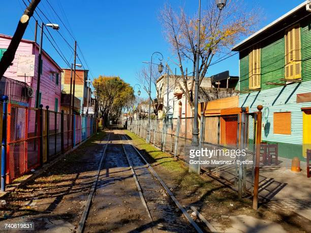 Railroad Track Amidst Bare Trees And Houses Against Sky