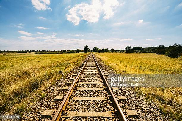 Railroad Track Amidst Grassy Field Against Cloudy Sky