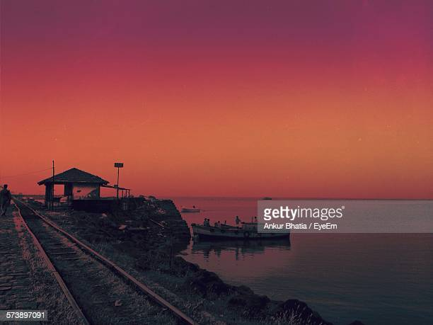Railroad Track By Beach Against Orange Sky