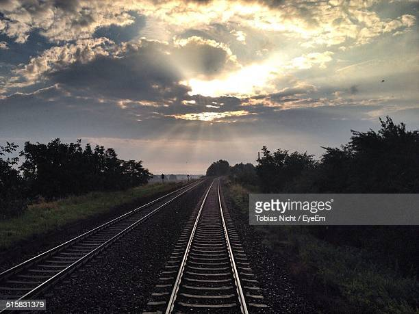 Railroad Tracks Against Cloudy Sky At Sunset