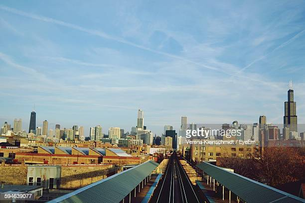 Railroad Tracks Amidst Modern Buildings Against Sky In City