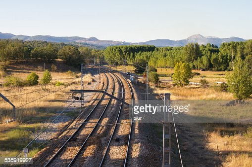 Railroad Tracks and Catenary next to Highway : Stock Photo