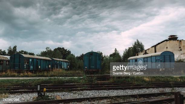 Railroad Tracks By Shunting Yard Against Cloudy Sky