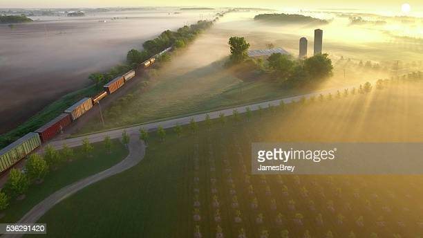 Railroad train rolls across breathtakingly beautiful, foggy landscape at sunrise
