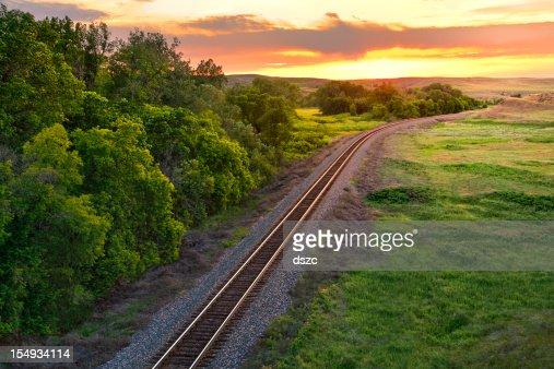 Railroad train tracks into the summer sunset, Montana, USA