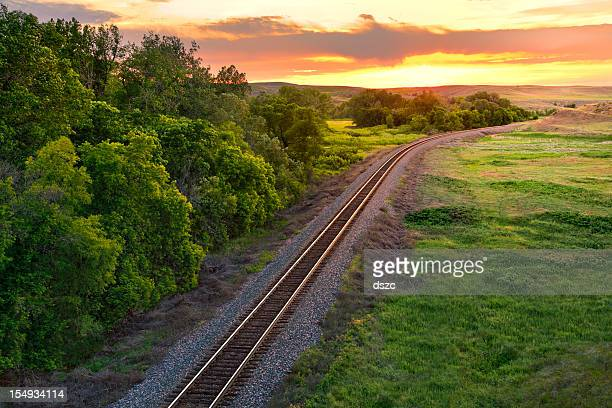 Railroad train tracks into the summer sunset, Montana, USA