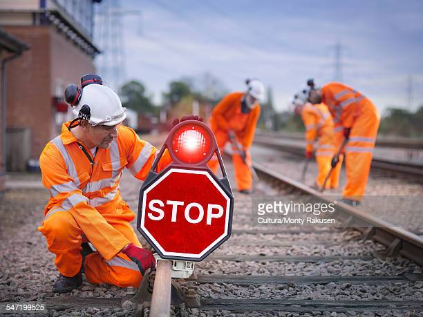 Railway maintenance workers on track with stop sign
