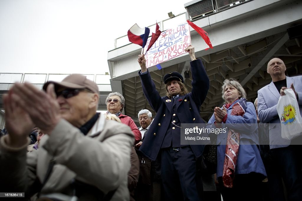 A railway man holds a banner as other members of the Czech opposition Communist (KSCM) party clap as they celebrate May Day on May 1, 2013 in Prague, Czech Republic. In addition to celebrations across the globe of the beginning of spring throughout the world, workers are gathering in city centers to annually vent their grievances and support their worker's unions.