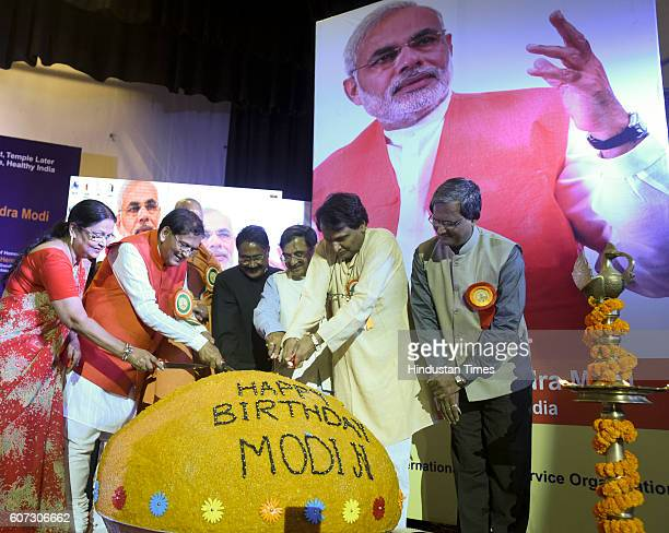 Railway Minister Suresh Parbhu Swami Avdheshanand Giri JI Maharaja Dr Bindeswar Patak and MP Tarun Vijay unveil a 365 kg 'ladoo' at the inauguration...