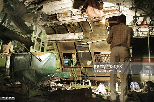 Railway officials inspect the debris of the first class compartment of a local train which was ripped open by a bomb blast at Khar Mumbai late 11...