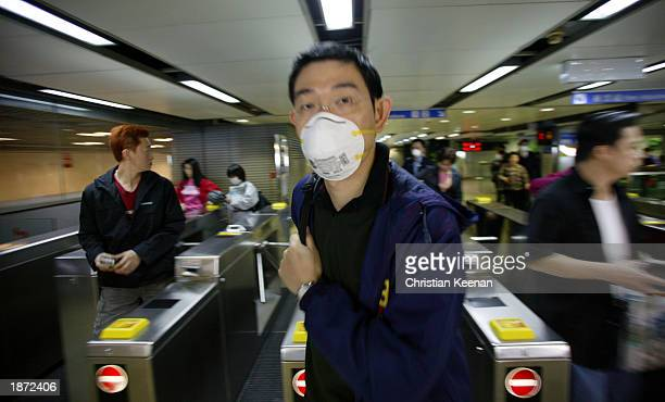 A railway passenger leaves a train station wearing a protective facemask March 26 2003 in Kowloon Hong Kong Kowloon Canton Railway passengers are...