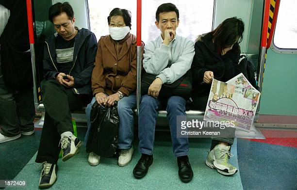 A railway passenger wears a protective facemask March 26 2003 in Kowloon Hong Kong Kowloon Canton Railway passengers are being given free facemasks...