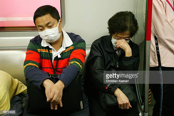 Railway passengers wear protective facemasks March 26 2003 in Kowloon Hong Kong Kowloon Canton Railway passengers are being given free facemasks if...