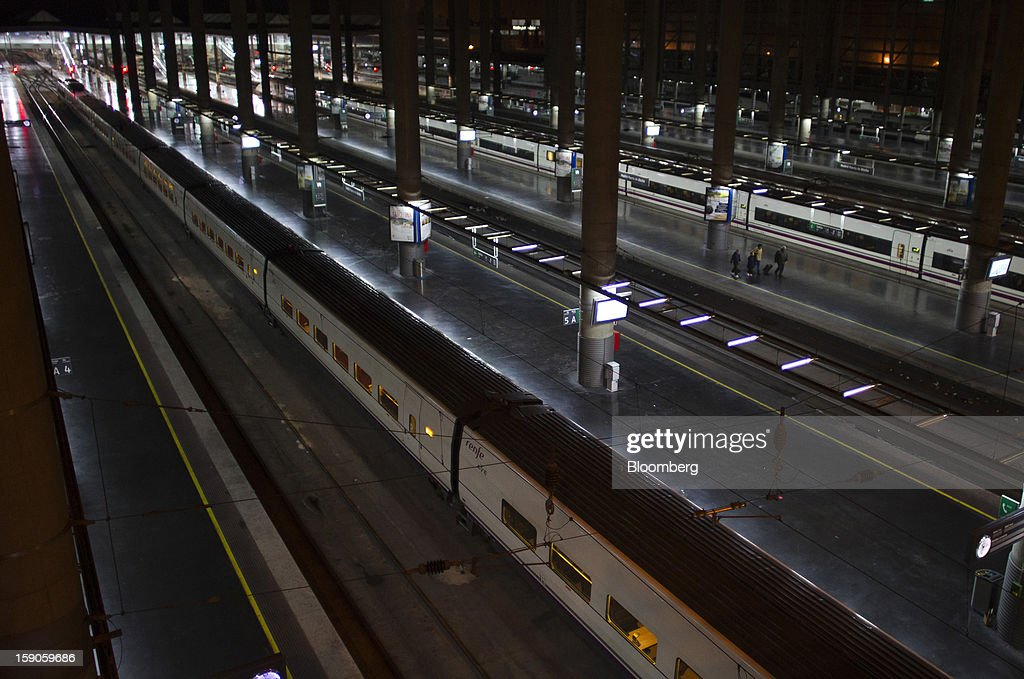 Railway platforms and trains are seen illuminated by electric lighting at Atocha station in Madrid, Spain, on Sunday, Jan. 6, 2013. In December, the Spanish parliament passed an energy law that imposed a 7 percent tax on electricity generation from Jan. 1 to plug the deficit. Photographer: Angel Navarrete/Bloomberg via Getty Images