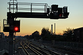 A red stop signal next to railway lines heading West at sunset.  Basingstoke railway station, Hampshire, UK.
