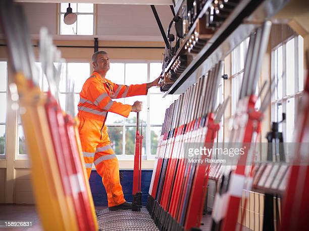 Railway signalman in signal box pulling lever