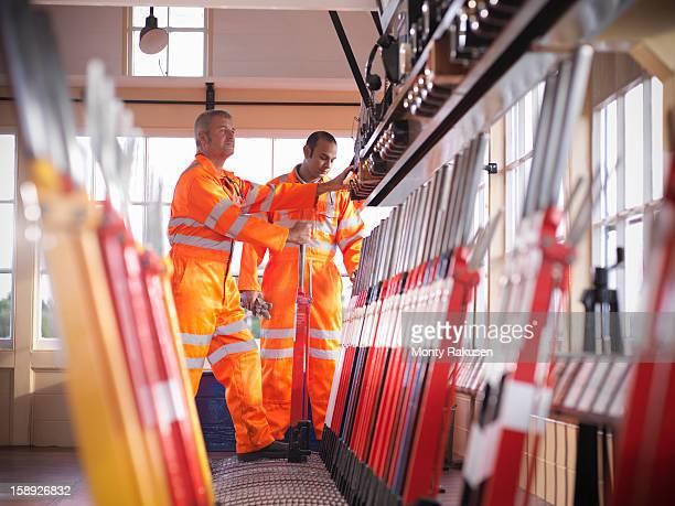 Railway signalmen in signal box pulling lever