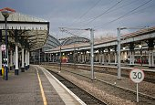 Two platforms on York Railway station with their original 19th Century canopies supported by greek columns.  Two larger arching canopies of metal and glass are in the background. Lamps are lit in the