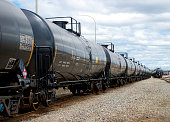 Black railway tanker cars of the type used to transport petroleum products. Several cars visible on two separate sets of tracks. Identification markings have been removed, only technical infomation re