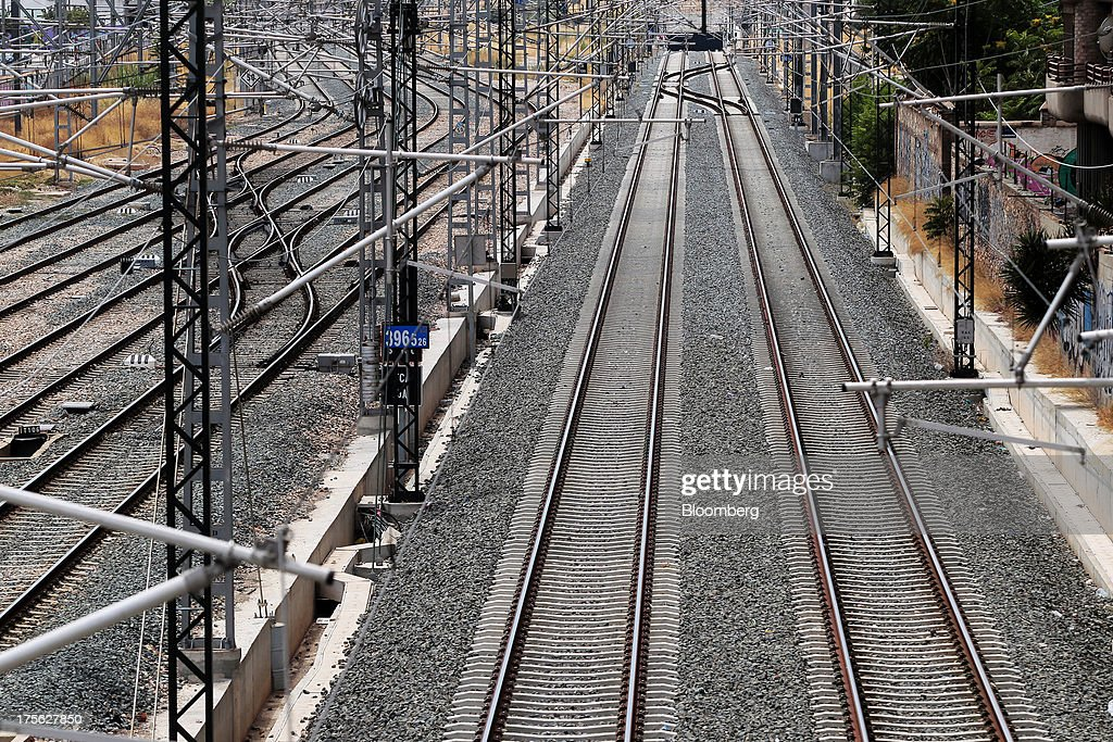 Railway tracks run beneath overhead power lines at Joaquin Sorolla train station in Valencia, Spain, on Saturday, Aug. 3, 2013. Spain's state-owned rail operator Renfe plans to cut almost 500 jobs, or 4% of staff, as early as this year, ABC reports, citing comments by Public Works Minister Ana Pastor. Photographer: Antonio Heredia/Bloomberg via Getty Images