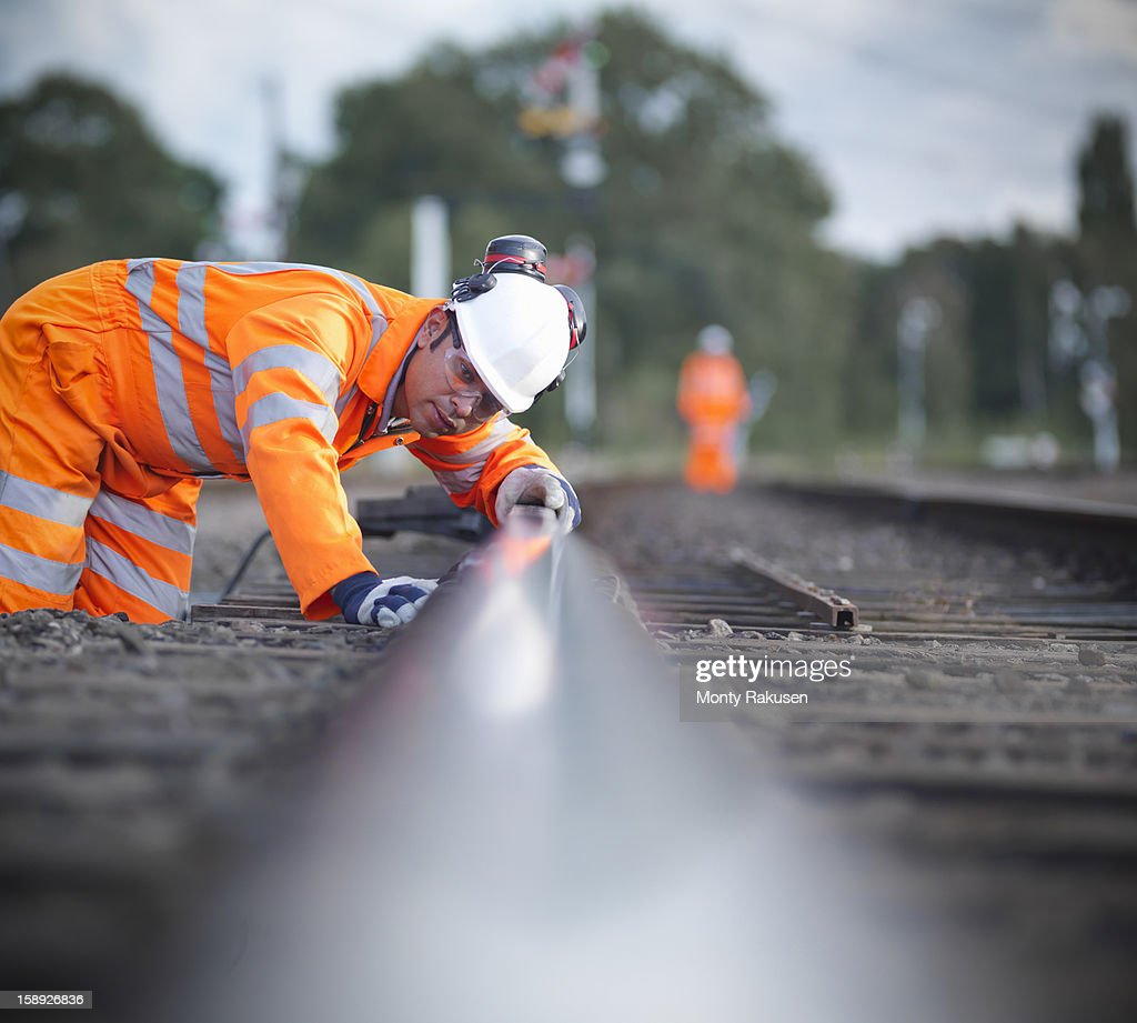 Railway worker checking railway track levels, surface level view