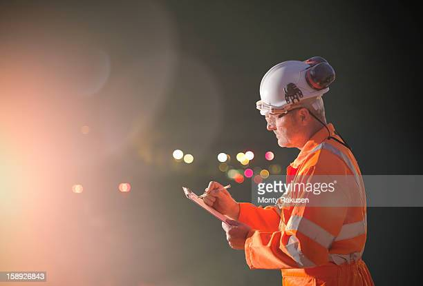 Railway worker making notes at night