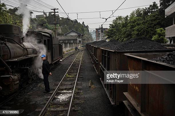 A railway worker stands by as a train carrying coal passes by next a coal powered steam engine in the workshop on March 27 2015 at a station in the...