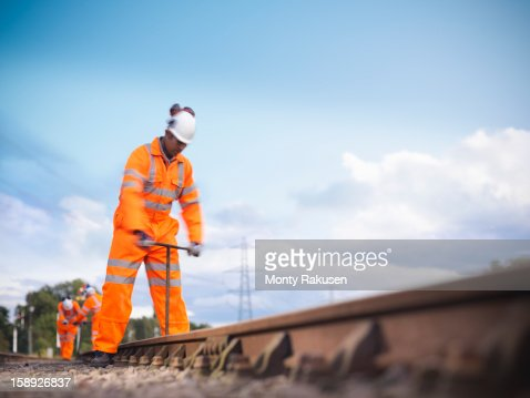 Railway worker using tool to work on railway tracks