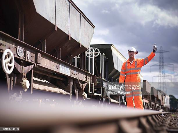 Railway worker wearing high visibility clothing waving alongside train